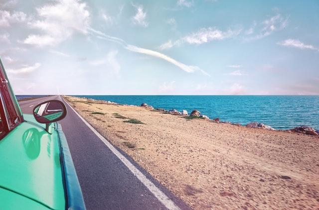 Groene auto langs de kust