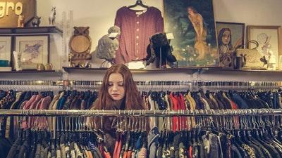 Meisje tussen kledingrekken