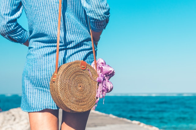 Vrouw op het strand in zomerse mode